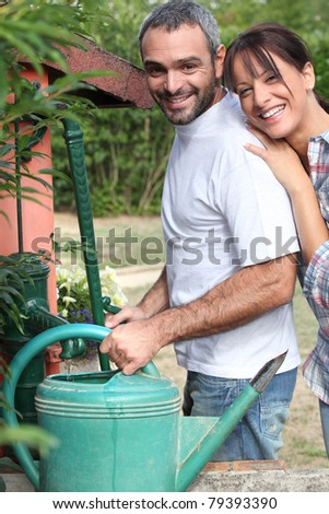 Couple filling up watering can - stock photo