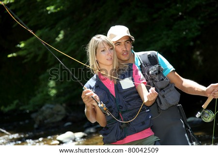 Couple fly fishing in river during summer vacation - stock photo