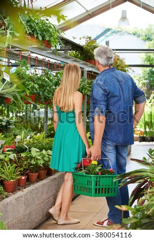 Couple from behind in nursery shop with shopping basket - stock photo