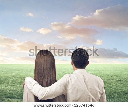 Couple, from the back, on a large lawn