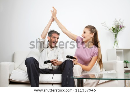 Couple giving a high-five to each other while having great time playing video game together - stock photo