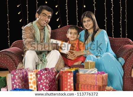 Couple giving gifts to their son on Diwali festival - stock photo