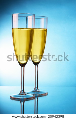 Couple glasses of champagne over blue background - stock photo