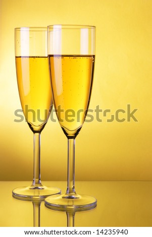 Couple glasses of champagne over yellow background