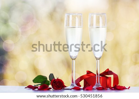 Couple glasses of champagne with beautiful red roses and gift on bright bokeh background. Love, valentine's day or celebrating concept