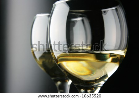 Couple glasses with white wine over black background