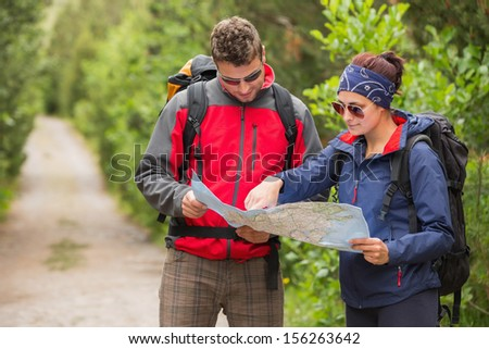 Couple going on a hike together looking at map in the countryside - stock photo