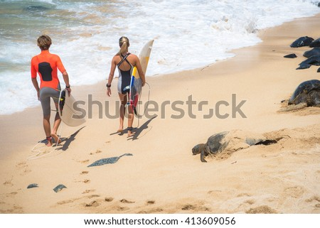 Couple going surfing on the beach during green sea tultle take rest, love natural concept - stock photo