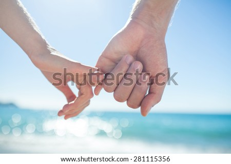 Couple hand in hand at the beach