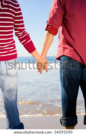 Couple hand in hand walking on the beach - stock photo