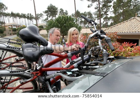 Couple hanging bicycles on bike carrier - stock photo