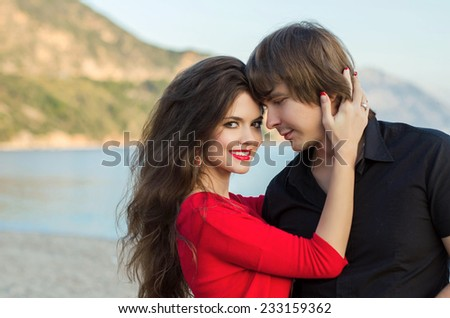 Couple happiness fun. Young couple embracing laughing on beach. Handsome man and beautiful woman in love. - stock photo