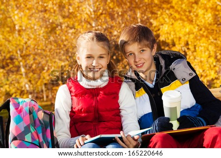 Couple happy smiling children, boy and girl sitting on the bench in autumn park holding books and coffee mug - stock photo