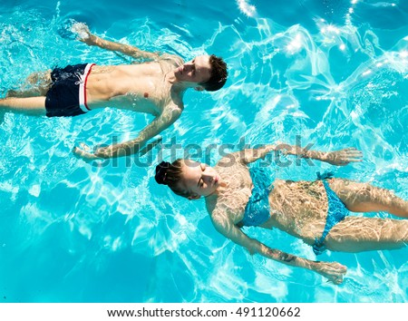 Couple has a rest in the pool with champagne. they are smiling, hugging and kissing.