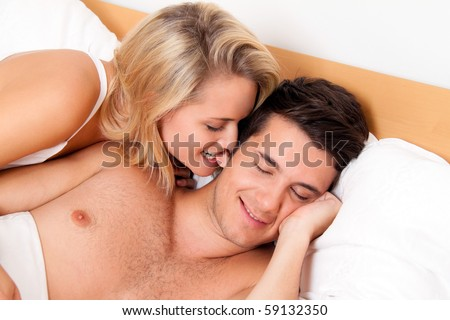 Couple has fun in bed. Laughter, joy and eroticism in the bedroom - stock photo