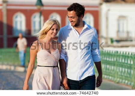 Couple having a city break in summer walking in the evening light - stock photo