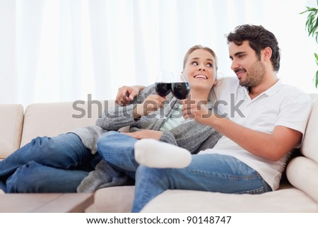 Couple having a glass of wine in their living room - stock photo