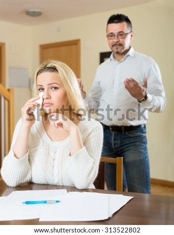 Couple having a quarell over financial problems. Wife is sitting at the table crying desperately while her husband is standing behind - stock photo
