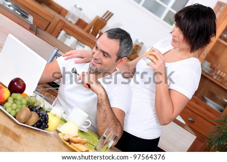 couple having breakfast and looking a computer - stock photo