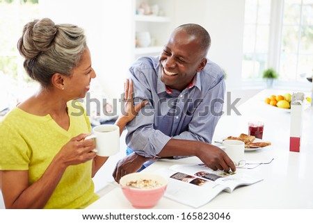 Couple Having Breakfast And Reading Magazine In Kitchen - stock photo