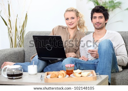 Couple having breakfast with computer