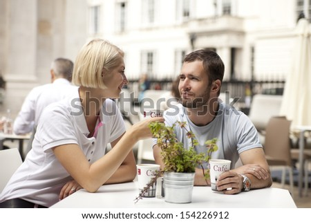 couple having coffee and flirting in street cafe - stock photo