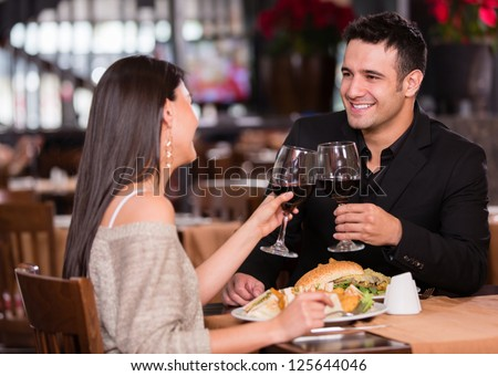 Couple having dinner at a restaurant and making a toast - stock photo