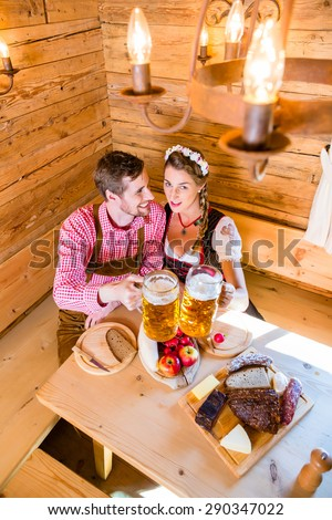Couple having dinner at mountain hut in alps drinking beer and eating cold cuts - stock photo