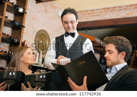 Couple having dinner in a luxury restaurant - stock photo