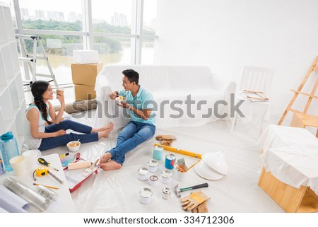 Couple having first lunch in their new apartment - stock photo