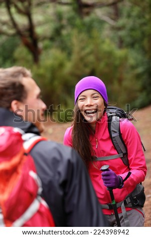 Couple having fun laughing hiking in forest. Multicultural woman and man hikers on hike in woods wearing backpacks outdoors in nature.