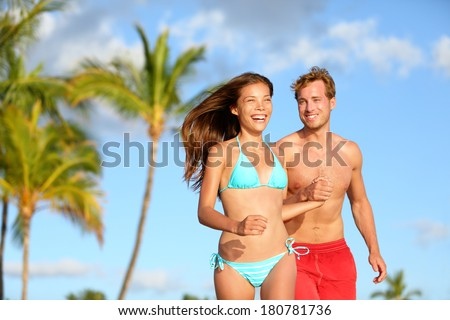 Couple having fun on beach vacation travel laughing happy running together playful and joyful. Woman in bikini and man in swimwear. Beautiful interracial lovers in love on honeymoon on Hawaii. - stock photo