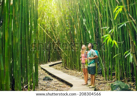 Couple having fun together outdoors on hike through amazing bamboo forest trail. - stock photo