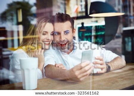 Couple having fun using smartphone at coffee shop - stock photo