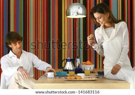 Couple having healty breakfast at home, eating cereals, fruits and drinking orange juice