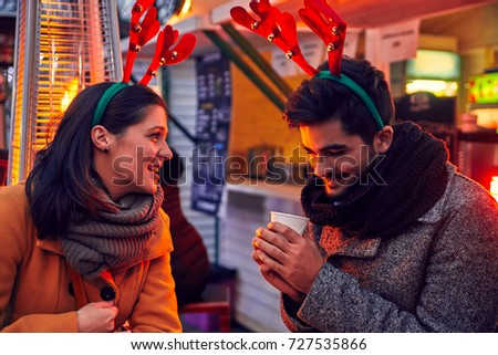 Couple Having Hot Drinks Outdoors On Winter Market