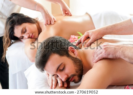 Couple having relaxing body massage in spa.Two therapists doing back massage on couple at the same time. - stock photo