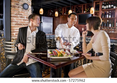 Couple having sushi in Japanese restaurant talking with chef - stock photo