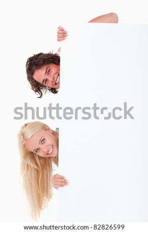 Couple hiding behind a whiteboard in a studio