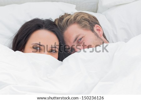 Couple hiding under the duvet in their bed - stock photo