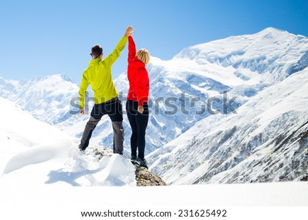 Couple hikers man and woman success in winter mountains, sport climbing. Inspiration and motivation in beautiful landscape. Fitness healthy lifestyle outdoors on snow Annapurna Himalayas, Nepal - stock photo