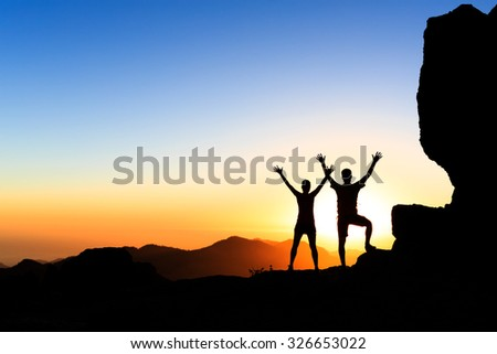Couple hikers success in sunset mountains, accomplish with arms outstretched. Man and woman on rocky mountain range looking at beautiful inspirational landscape view, Gran Canaria Canary Islands. - stock photo