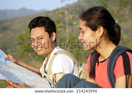 Couple hikers taking map