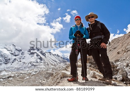 Couple hiking in himalayas mountains in Nepal. Young people traveling in Asia, man and woman trekkers on trail in wilderness. - stock photo