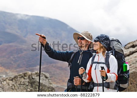 Couple hiking in himalayas mountains in Nepal. Young people traveling in Asia, trekkers on trail in wilderness. - stock photo