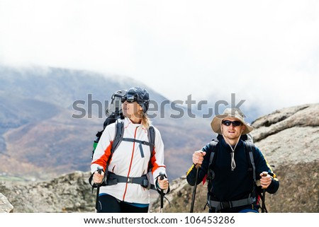 Couple hiking in mountains, Himalayas in Nepal. Man and woman trekking in summer nature outdoors. Young people traveling in Asia, trekkers on trail in wilderness. - stock photo