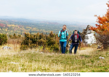 Couple hiking in nature with backpacks - stock photo