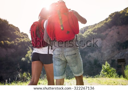 Couple hiking. View from behind. - stock photo