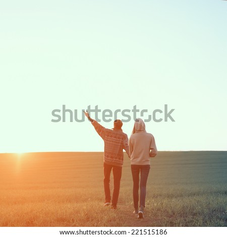 Couple hipsters goes hand on a background sunset - stock photo