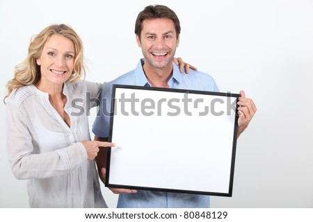 Couple holding a blank board ready for image or text - stock photo